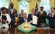 President Donald Trump center, posthumously pardons Jack Johnson, boxing's first black heavyweight champion, during an event in the Oval Office of the White House in Washington, Thursday, May 24, 2018. Trump is joined by, from left, Linda Haywood, who is Johnson's great-great niece, heavyweight champion Deontay Wilder, Keith Frankel, Sylvester Stallone, former heavyweight champion Lennox Lewis, and World Boxing Council President Mauricio Sulaiman Saldivar. (AP Photo/Susan Walsh)