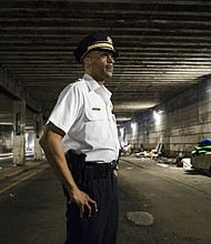 Philadelphia Police Commissioner Richard Ross overseas the clearing of an encampment under a bridge in Philadelphia, Wednesday, May 30, 2018. The city's homeless packed up their few belongings as sanitation workers cleaned and power washed what had been a heroin encampment only moments before. (AP Photo/Matt Rourke)
