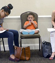 In this May 15, 2018, file photo, Joan Herrera, center, sits and waits as his mother Andrea Batista Garcia, left, and Marlene Gonzales, fill out job applications while attending the Great Northeast 2018 Job Fair at Capriotti's in McAdoo, near Hazleton, Pa. The U.S. government issues the May jobs report on Friday, June 1. (Ellen F. O'Connell/Hazelton Standard-Speaker via AP, File)