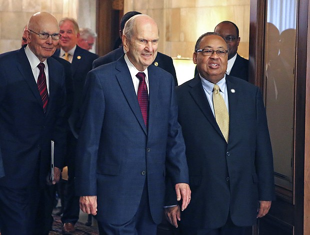 In this May 17, 2018, file photo, Mormon church President Russell M. Nelson, center, and Leon W. Russell, chairman of the NAACP board of directors, right, walk into a news conference, in Salt Lake City. The Mormon church on Friday, June 1, 2018, will celebrate the 40th anniversary of reversing its ban on black people serving in the lay priesthood, going on missions or getting married in temples, rekindling debate about one of the faith's most sensitive topics. (AP Photo/Rick Bowmer, File)
