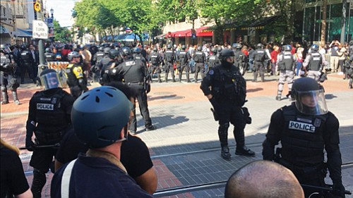Portland police corral protestors for mass detainment during an anti-Trump demonstration last year, not allowing them to leave until they handed over their IDs and were photographed. The American Civil Liberties Union has been granted class action status to allow the nearly 400 people held during the June 4, 2017 protest to join an ACLU lawsuit which claimed the police action violated the Constitution for detaining people without cause.