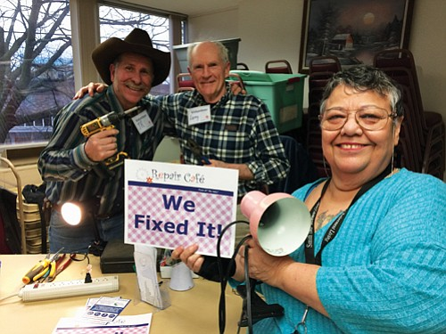 Volunteers with the Clark County Repair Cafe help a participant repair her lamp.