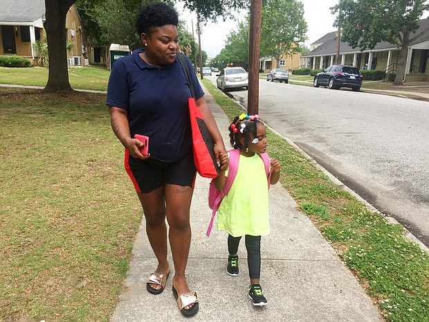 In this May 17, 2018 photo, Shannon Brown, 29, walks with her four-year-old daughter, Sai-Mya, in Charleston, S.C. Brown lives in public housing and could face a steep increase under a HUD proposal that would raise rents for millions of low-income individuals and families. (AP Photo/Juliet Linderman)