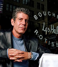 This Dec. 19, 2001 file photo shows Anthony Bourdain, the owner and chef of Les Halles restaurant, sitting at one of the tables in New York. On Friday, June 8, 2018, Bourdain was found dead in his hotel room in France, while working on his CNN series on culinary traditions around the world. (AP Photo/Jim Cooper,File)