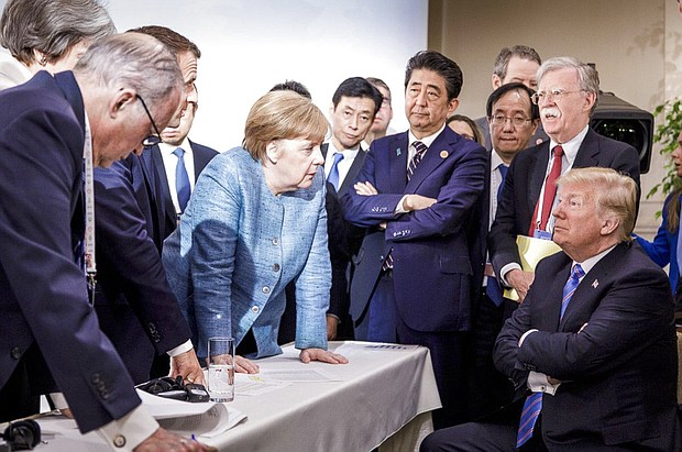 German Chancellor Angela Merkel, center, speaks with U.S. President Donald Trump, seated at right, during the G7 Leaders Summit in La Malbaie, Quebec, Canada, on Saturday, June 9, 2018. (Jesco Denzel/German Federal Government via AP)