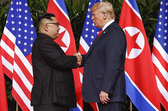 Donald Trump approached from the right, striding down the long portico at the colonial-era Singapore resort. Kim Jong Un, dressed ...