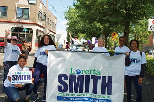 City Council candidate and current Multnomah County Commissioner Loretta Smith waves to onlookers and her supporters carry signs of solidarity at Saturday's Juneteeth parade.