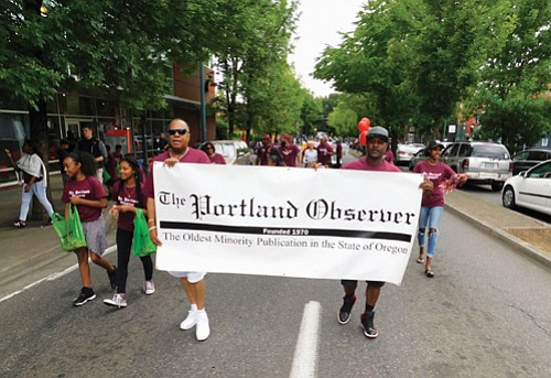 Representatives of the Portland Observer, Oregon's longest continuous minority-owned newspaper, march down Martin Luther King Jr. Blvd.