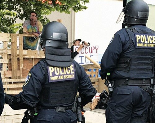 Federal police officers stand guard after clearing a path to the U.S. Immigration and Customs Enforcement (ICE) holding facility on Southwest Macadam Avenue on Thursday, June 27. Nine protestors blocking the entrance of the building were arrested.