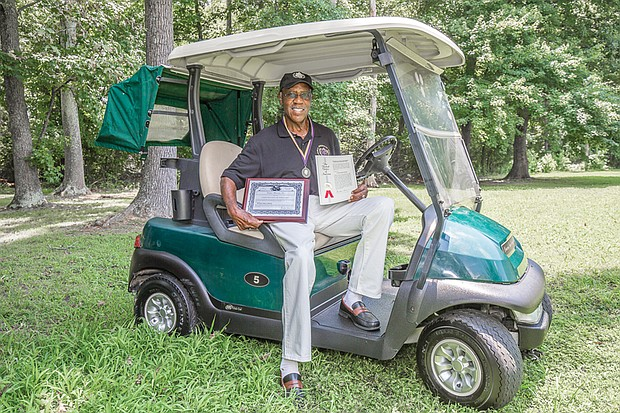 John Houze Jr. holds in his right hand the patent for his retractable golf canopy that is attached to the roof of his golf cart. Mr. Houze also holds the application for the patent, which was filed two years ago and granted in May 2018.