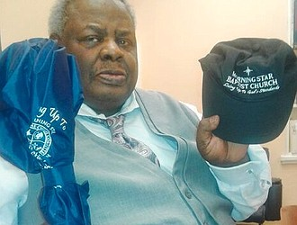 The Rev. Ernest Blue Jr. shows the umbrella and baseball cap he received from Morning Star Baptist Church's pastor after preaching a guest sermon on July 1.