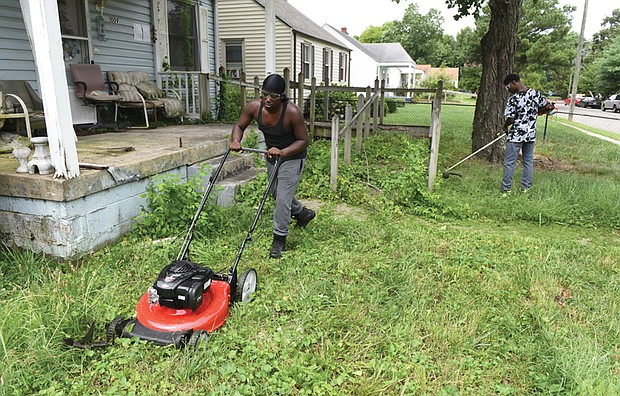 Michael Beckley, 17, mows the lawn while Xavier Edmonds, 16, whacks weeds last Saturday at a vacant home on Garber Street in Fulton before seeking customers for paying jobs through the 4-H Lawn Maintenance Program started by Wyatt Kingston.