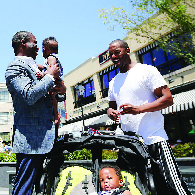 CELEBRATING A RICHMOND ICON-Richmond Mayor Levar M. Stoney holds 10-month-old Nasir Jackson while the infant's dad, Timothy Jackson, and twin brother, Dakari, pause beside the statue of Richmond businesswoman Maggie L. Walker during Saturday's celebration Downtown honoring her 154th birthday.