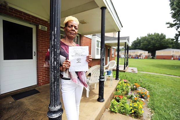 Gwendolyn Harris holds a notice from Richmond Redevelopment and Housing Authority telling her she must come to the Creighton Court management office to sign a lease amendment that embodies the new regulation banning smoking.