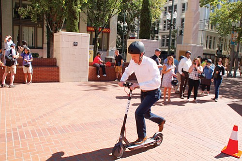 A local man gets a free helmet and scooter riding lesson at Pioneer Courthouse Square, downtown, after Bird, one of two electronic scooter companies permitted to set up shop in Portland, introduced the service on Thursday.