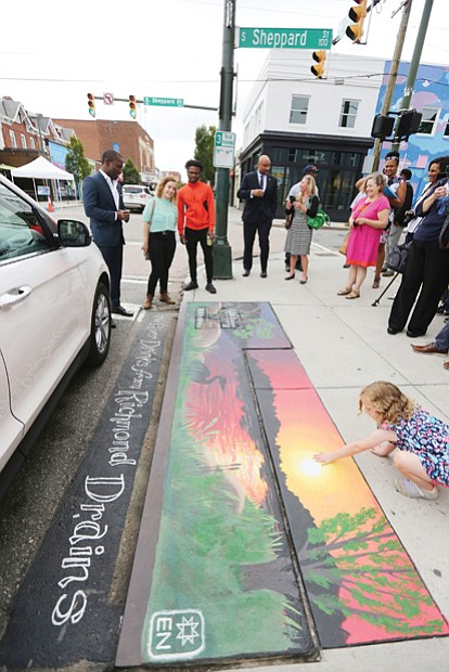 "Mayor Levar M. Stoney takes part in a tour of the new artwork decorating four storm drains in Carytown. Here, the group is viewing Elise Neuschler's ""Deep Texas Beach"" mural at Cary and Sheppard streets.