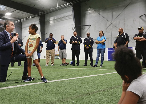 Gov. Ralph S. Northam takes a knee to hear the question posed by 9-year-old Kimoni Jenkins, 9, Wednesday morning during his visit to the Richmond Police Athletic League Summer Camp in North Side. The governor spent an hour fielding questions from the 130 youngsters at the camp.