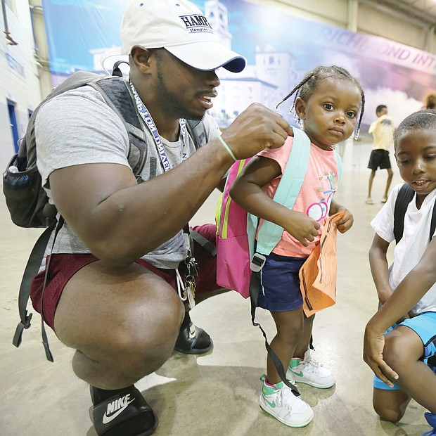 Justin-Mychal White, 28, adjusts the straps of his 2-year-old daughter Reagan's new backpack last Saturday at the 10th Annual Back-to-School Rally sponsored by the Northside Coalition for Children. Reagan's older brother, Jeremiah seems like an old pro with his new backpack. The 6-year-old will be a first-grader at Longdale Elementary School in Henrico County in the fall. The nonprofit coalition gave away the backpacks stuffed with school supplies at the Richmond Raceway.