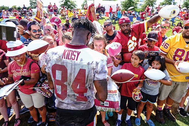 Hundreds of fans and autograph seekers flocked to the Washington professional football team's training field to hobnob with their favorite players during last Saturday's Fan Appreciation Day. Following practice, wide receiver Darvin Kidsy signs footballs and other team paraphernalia for fans of all ages.
