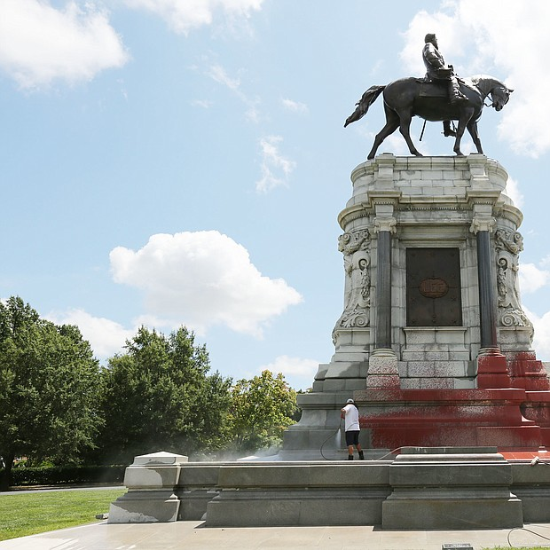 Workers with Envirowash scrub and power wash the base of the Lee statue on Monument Avenue last Saturday after the Confederate statue was vandalized sometime overnight between Aug. 3 and 4. The state Department of General Services, which owns and maintains the statue at Monument and Allen avenues, paid more than $4,400 for the cleanup.