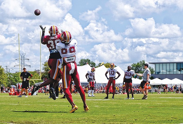 Hundreds of fans and autograph seekers flocked to the Washington professional football team's training field to hobnob with their favorite players during last Saturday's Fan Appreciation Day. Safety Kenny Ladler, left, cuts in to snatch a catch from wide receiver Cam Sims.