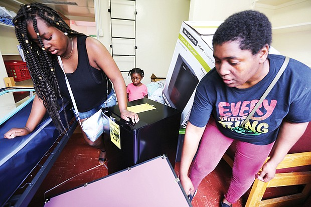 Left, Kavin Baines, 18, of Portsmouth gets a helping hand from her mother, Miki Baines, during last Saturday's freshmen move-in at Virginia Union University. Orientation for members of the Class of 2022, along with classes for new students, started Monday on the Lombardy Street campus. Future student Kenzie Creekmur watches and takes notes about dormitory life in the background.