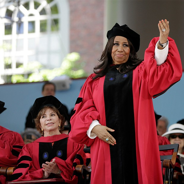 Ms. Franklin acknowledges the cheering crowd as she stands to receive an honorary degree at Harvard University during the May 2014 commencement ceremony.