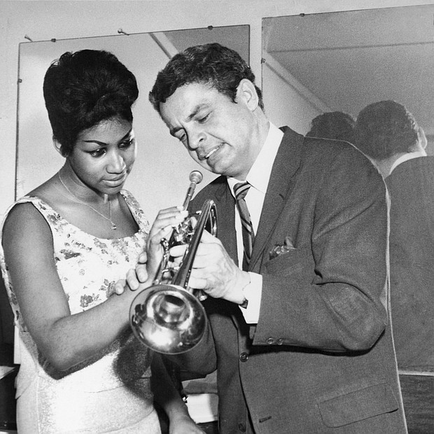 Aretha Franklin is taught how to properly play a trumpet by Canadian trumpeter Maynard Ferguson at Chicago's Sutherland Hotel in 1964.
