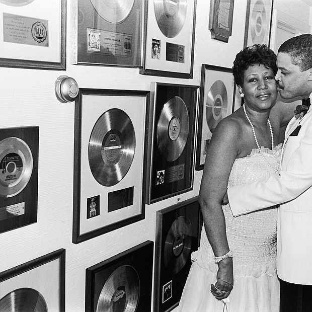 Aretha Franklin receives a kiss from beau Willie Wilkerson at Franklin's Birthday Celebration held at her sprawling suburban Detroit estate in 1987.