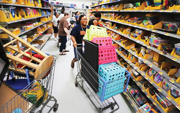 Huguenot High School teacher Catrina Cheeks happily fills her shopping cart with school supplies Wednesday at a Walmart store in South Side. She was among an estimated 200 teachers from Huguenot, Elkhardt-Thompson Middle and Westover Hills Elementary schools surprised with a $200 shopping spree at the Sheila Lane store.
