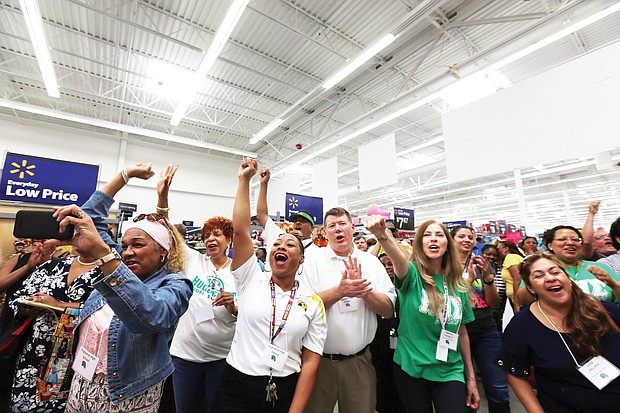 "Huguenot High School Principal Robert ""Rob"" Gilstrap, center, joins in the celebration after teachers from the school learn they each have been awarded a $200 shopping spree. Location: The Walmart store on Sheila Lane, just a short distance from the school at 7945 Forest Hill Ave."