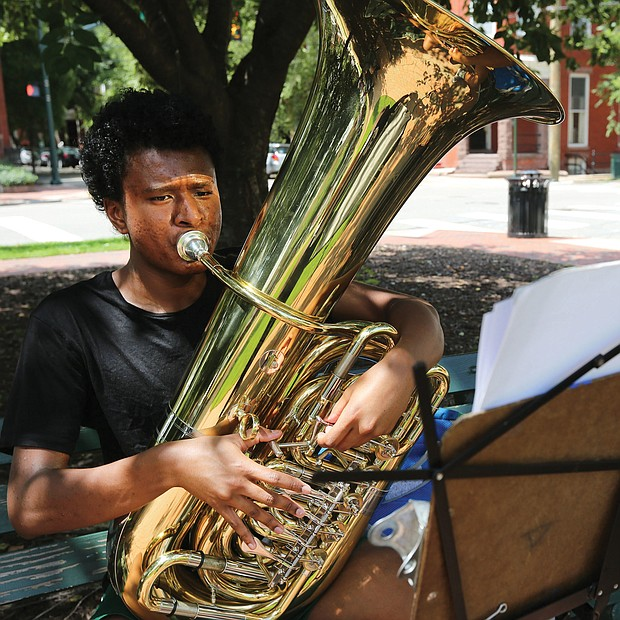 Practice, practice, practice Terence Burks, 18, of Williamsburg practices his tuba at the corner of Harrison Street and Park Avenue outside the Music Department at Virginia Commonwealth University in The Fan. The second year music education major was getting ready for an audition. Practice makes perfect. (Regina H. Boone/Richmond Free Press)