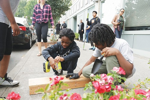 10 year-old Dominique Stewart (left) and Tryston Birdges, 12, help build flower and vegetable planters along the North Williams and Russell Street corridors as part of an Urban League of Portland project to celebrate the historic community contributions of African Americans in Portland.  The project was made possible by a grant and partnership from the Portland Bureau of Transportation.