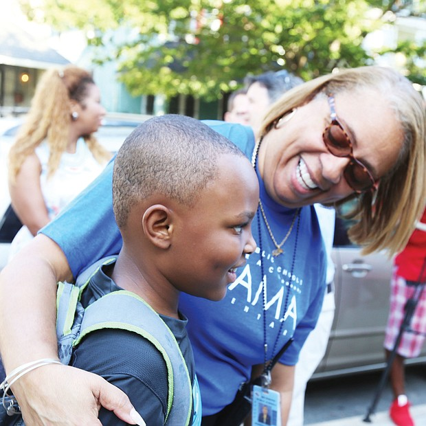 First day welcome: Barack Obama Elementary School Principal Jennifer Moore welcomes 7-year-old Christopher Pleasants to the first day of school Tuesday. Opened in 1922, the Fendall Avenue school had been named for a Confederate general. (Regina H. Boone/Richmond Free Press)