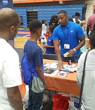 "Miquel Moe, an electrical engineer from the NASA Goddard Space Flight Center in Greenbelt, Maryland, an exhibitor at the STEM Extravaganza presented the hands-on exhibit, ""Ready, Set. Go to Space."" Scores of interested children came to the NASA table to make satellites with wooden sticks, styrofoam and aluminum foil as they learned of the importance of their involvement in science and engineering."