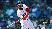 Mookie Betts of the Boston Red Sox hits a sacrifice fly to bring in a run during last Sunday's game against the New York Mets in Boston.