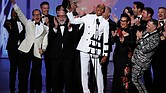 "RuPaul Charles, originator of ""RuPaul's Drag Race,"" is cheered by a bevy of supporters while accepting the Emmy for outstanding reality-competition program."