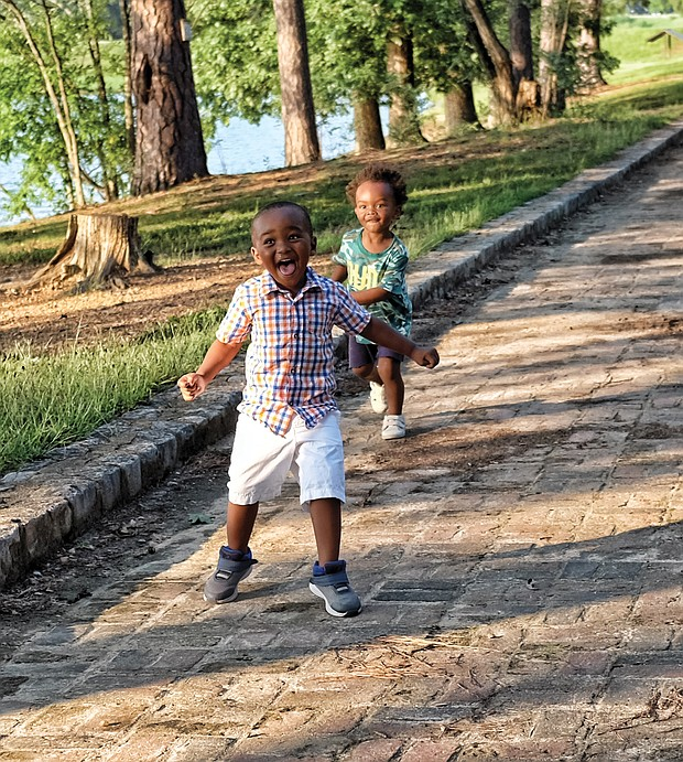 Two-year-old cousins Khamryn Tyler, left, and Xavier Taylor enjoy the sunshine and running along a brick walkway at Shields Lake in Byrd Park on Wednesday during an outing with their moms, Benneka Tucker and Leesa Taylor, and their grandfather, Emanuel Crawford. Area residents welcomed the nice weather after the string of overcast days and sheets of rain associated with the hurricane.