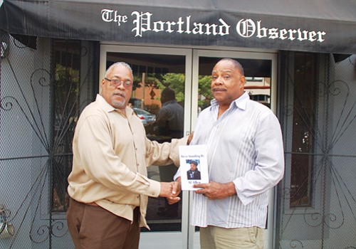 "Marcus Branch of Portland (right) presents Portland Observer Publisher Mark Washington with a personalized copy of Detroit journalist Al Allen's book ""We're Standing By."" Branch met with Allen, a longtime TV anchor and reporter, at the National Association of Black Journalists Convention in Detroit where the book was signed, last month."