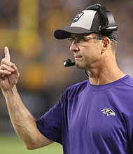 Ravens head coach John Harbaugh signals a play onto the field during the team's 26 - 14 win over the Steelers at Heinz FIeld on September 30, 2018.