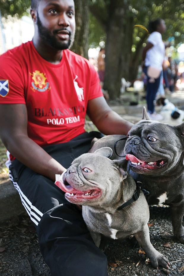 Paws pause: Marcus Perry and his two French bulldogs, Hugo and Keiko, take a break at the inaugural Richmond Dog Festival last Saturday at 17th Street Market in Shockoe Bottom. The festival, benefiting the Enrichmond Foundation, brought together dog lovers and their dogs for music, demonstrations, a pet fashion show, food, music and a bevy of vendors who serve Richmond's pet community, including dog sitters, trainers, rescue leagues and makers of dog treats. (Regina H. Boone/Richmond Free Press)