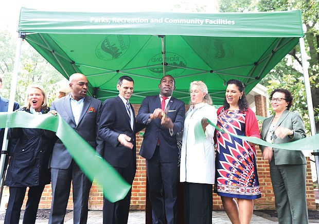 Mayor Levar M. Stoney, center, cuts the ribbon to reopen Monroe Park on Sept. 27. He is flanked by VCU President Michael Rao and Alice M. Massie, president of the park's new governing body, the Monroe Park Conservancy, and other dignitaries. The nearly 8-acre space was Richmond's first public park when the city acquired the land in 1851. The reopening will allow churches and other groups to resume serving meals to the homeless on weekends. The Monroe Park Conservancy has a 30-year lease with the city to operate and manage the park in cooperation with the city's Department of Parks, Recreation and Community Facilities. (Regina H. Boone/Richmond Free Press)