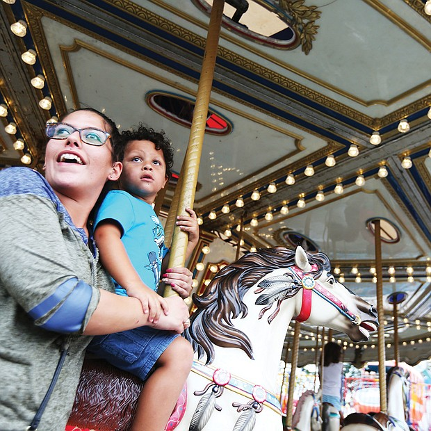Fun at the fair: Gabby Wood takes a whirl on a merry-go-round with her 4-year-old son, Levi, last Sunday at the State Fair of Virginia. The annual event, featuring exhibits, farm animals, midway rides and food, runs through Sunday, Oct. 7, at the Meadow Event Park in Caroline County. (Regina H. Boone/Richmond Free Press)