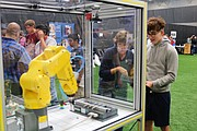 Joliet Junior College professor Mary Sue Gurka (left) guides Minooka High School senior Cole Gerovac (right) in how to use the Fanuc Robotics LR Mate 200 iD/4S during Joliet Junior College's fifth annual Manufacturing Day, held Oct. 9 at the college's main campus in Joliet. The robot is used in a number of industrial applications, including the assembly of parts and welding in automotive.