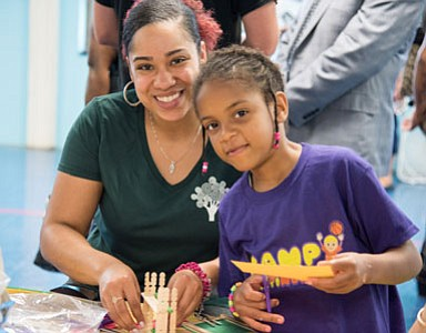 "Britney Pitts, Parent University I Coordinator, doing Arts & Crafts with a youngster at ""Parent University,"" a Promise Heights program."