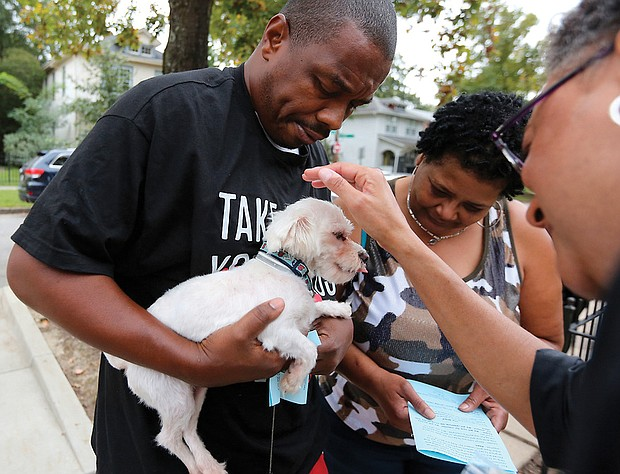 Blessing of the animals: The Rev. Phoebe A. Roaf, rector of St. Philip's Episcopal Church, places her hand in prayer on Renz, the 3-year-old pet of Bernard Brown and Patricia Smith, during last Saturday's annual Blessing of the Animals service at the North Side church. Each pet received a St. Francis medal and treats. The services typically are held on or around the Oct. 4 Feast Day for St. Francis of Assisi, the patron saint of animals. (Regina H. Boone/Richmond Free Press)