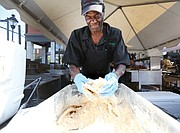 David Senegal of Croaker's Spot restaurant batters some fish before frying it for the tasty fish boats featured on the menu at the 2nd Street Festival. (Regina H. Boone/Richmond Free Press)