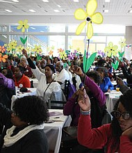 "Attendees raise their flowers during the ""Promise Garden"" ceremony. Each colored flower distinguishes how the disease has affected the person's life. People holding yellow flowers are currently caregivers of someone with the disease; people holding blue flowers have the disease; orange represents supporters; and purple represents people who have lost a loved one to the disease."
