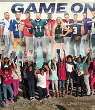 The Sunday Night Football Bus made a stop at Webster M. Kendricks Recreation Center in West Baltimore on Friday, October 12, 2018, thanks to a partnership between Comcast and the Boys & Girls Clubs of Metropolitan Baltimore. (Above) Youth from West Baltimore cheer with raised hands beside the Sunday Night Football Tour Bus.