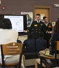 Lt.j.g. Bryan Cooley, from Sturgis, South Dakota (center) assigned to the Ohio-class ballistic missile submarine USS Maryland (SSBN 738), speaks to children at Fort Meade Teen Center about submarine life as part of Maryland Fleet Week and Air Show Baltimore. MDFWASB is Baltimore's celebration of the sea services and provides an opportunity for the citizens of Maryland and the City of Baltimore to meet Sailors, Marines and Coast Guardsmen, as well as see firsthand the latest capabilities of today's maritime services.